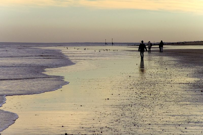 The sunset reflects off the damp beach in Hornsea. A family walks slowly into the distance. Taken on the 30th of December 2004.