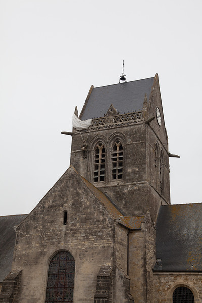 Saint Mere Eglise was the site of paratrooper landings behind enemy lines at 0140 on June 6. Many paratroopers were shot down as they landed. One, John Steele, landed on the town's Church steeple. He survived the war. In memory of the allied assault, townspeople have kept a replica of Steele on the Church steeple to this day.