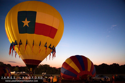 A hot air balloon is shown participating in the Plano Balloon Festival.  The Plano Balloon Festival takes place in the Fall each year.