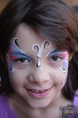 Portrait of a Little Girl with brown hair that has her face painted.