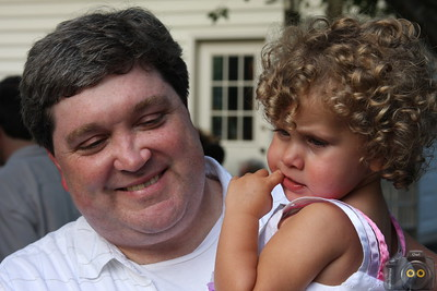 Portrait of a black hair man holding a little girl with brown curly hair.