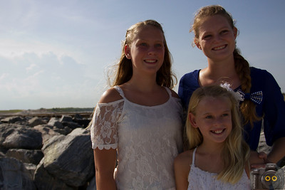 Family portrait of three girls at the beach in front of some rocks.