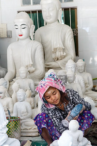 Burmese girl polishing marble statues in Mandalay, Myanmar