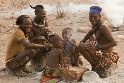 Himba men watch women make breakfast, Namibia