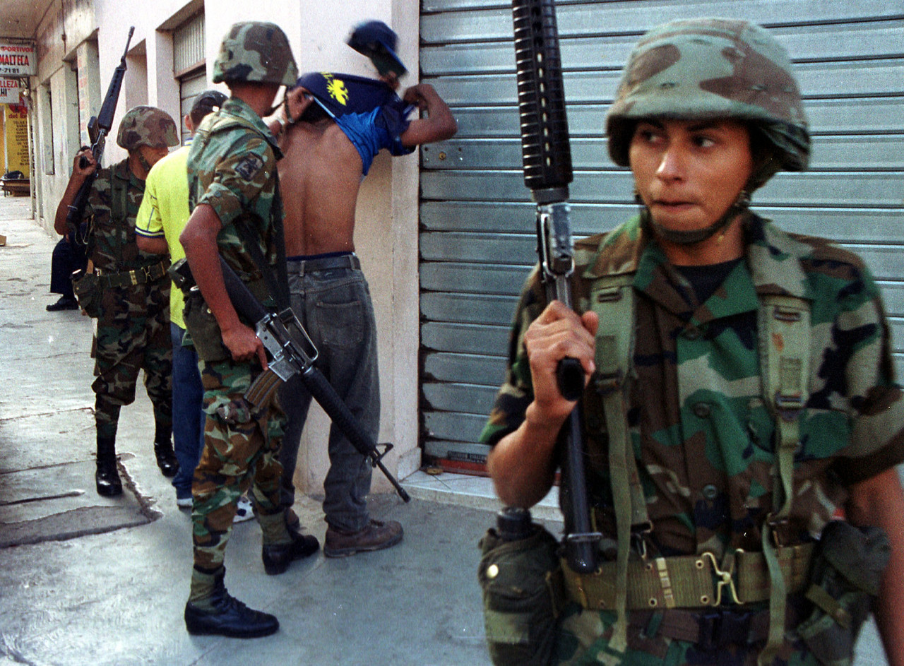 "Honduran soldiers search a subject for gang related tatoos August 18, 2001 in Tegucigalpa, Honduras. The Military was called out to assist police after a shoot-out between rival gangs left 7 injured on August 13. 126 soldiers patrol the steets today due to concerns  that more violence could erupt as the street  gang ""Mara 18"" had threatened that they would kill 18 people on this date.  REUTERS,/ Adam Bernstein"