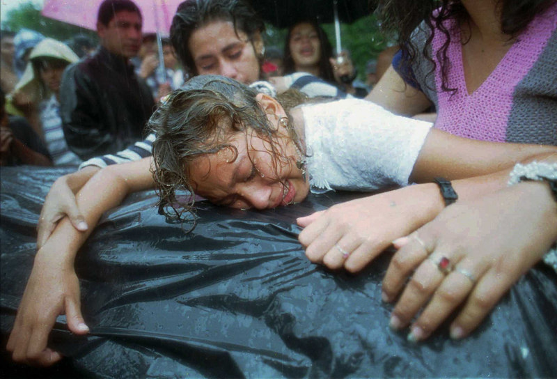 """Heidi Veronica Pineda, 17, weeps on the coffin of her boyfriend, Lucas Rafael Pineda Gonzalez, 23, at his funeral in Santa Tecla, El Salvador, September 1995. Pineda, known as """"Psycho"""" by members of the Mara Salvatrucha gang, was reportedly shot in the head by a vigilante group. (AP Photo/Douglas Engle)"""