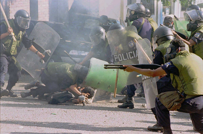 Members of the riot squad of El Salvador's National Civil Police  open fire with shotguns, and teargas and subdue a protestor with force during disturbances Thursday, November 23, 1995 in San Salvador, El Salvador. Police clashed  with former soldiers who took over the offices of the Disabled War Veterans' Fund, where they held the employees hostage demanding fulfillment of the 1992 peace accords, which ended the 12 year civil war. One protestor was killed.(AP Photo/Douglas Engle