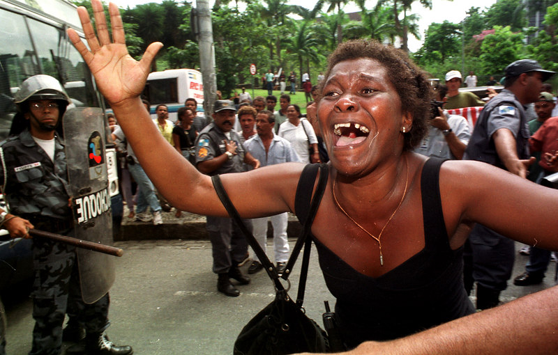 A woman screams in front of riot police during a fisherman's protest in downtown Rio de Janeiro, Brazil, Monday, January 20, 2000. Dozens of fisherman protested in front of the building of Petrobras, the government-owned oil company, demanding more compensation for an oil spill in January 2000.(AP Photo/Douglas Engle)