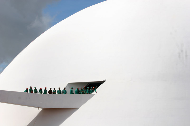 Construction workers attend the inauguration of the National Museum of Brasilia in Brasilia, the planned capital of Brazil, March 31, 2006. Brasilia, designed by Lucio Costa with buildings and monuments designed by Oscar Niemeyer, was Inaugurated in 1960 by President Juscelino Kubitschek. The site in central Brazil was chosen to help develop the interior of the nation and to move the capital away from the coast as a security measure against attack.