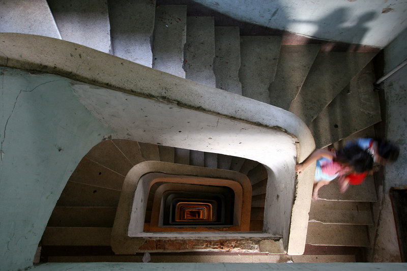 With no working elevator, residents descend the stairway of an abandoned building in central Sao Paulo, Brazil, Jan. 18, 2006. Thousands are squatting in the 22 floor abandoned building commonly referred to as the Prestes Maia occupation, after the avenue it is on in central Sao Paulo.  The squatters are part of the Brazil's sem teto or 'roofless' movement - an urban coalition that is gathering momentum in cities across the country. The movement is the urban equivalent to the better-known  MST, Brazil's Movimento dos Sem Terra or Landless Movement which has spearheaded the campaign for land reform since the 1980s. The MST defends Brazil's impoverished rural workers and reclaims unproductive land for the dispossessed. The MSTC reclaims buildings for the homeless and for low income workers, many who work in the informal economy, who are just not able to enter the official housing market.