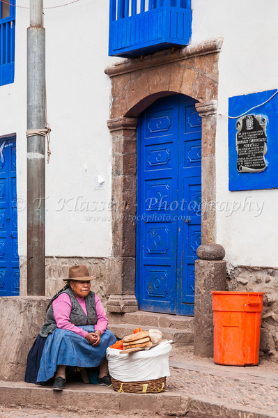 A Peruvian lady in traditional dress selling bread in the Pisac market in front of a blue door in the Urubamba Valley, Peru, South America.