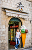 A young girl on the cell phone eating ice cream in the old historic city of Dubrovnik, Croatia.