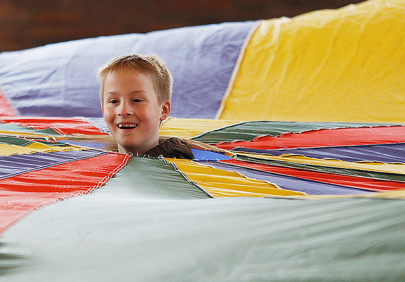 Fort Branch third-grader Cayden Murray pops his head out of the center of the large parachute he and his classmates were using to illustrate recycling techniques during the 14th annual Earth Camp at Camp Carson. More than 500 third-graders from Gibson, Posey and Vanderburgh counties took part in the three-day program where they learned about recycling and other earth-related issues.