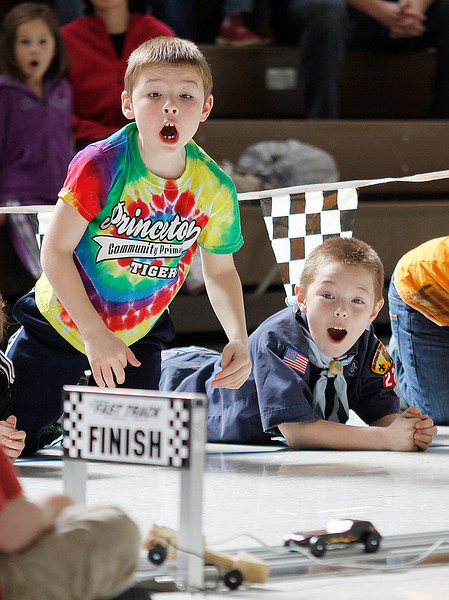 Nine-year-old Eli Krause, left, and Kane Fuhrer react to a wreck on the track during Cub Scout pack 222's Pinewood Derby races at St. Joseph School In Princeton. The scouts carve the cars out of a standard size block of wood then can add weights, paint and decals, in compliance with Boy Scouts of America rules, to try and improve the speed on the gravity fed track.