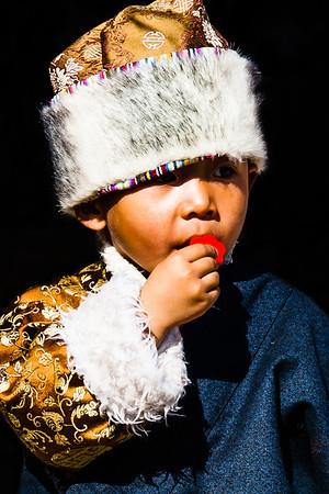 A Tibetan boy, dressed in his Losar chuba, sucking on a lollipop.