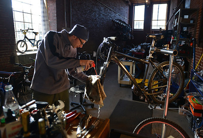Karl Borne works on a bicycle at the Merrimack Valley YMCA's BiciCocina, or Bicycle Kitchen, at the Everett Mill on Dec. 14, 2013.