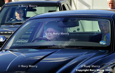 Queen Elizabeth II of England drives her own car with Duke of Edinburgh driving himself in the background.