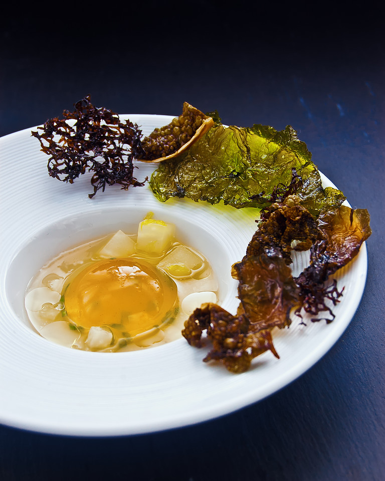 A Chondrus seaweed jelly globe in an oriental spiced bouillon with orange poached celeriac cubes and crunchy seaweeds chips