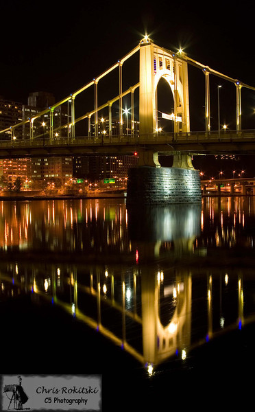 A reflection of the Roberto Clemente bridge (6th Street Bridge) connecting downtown Pittsburgh to the North Shore, near PNC Park.  I was standing on the North Shore to capture the night skyline reflecting in the Allegheny River.