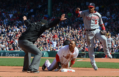 The Boston Red Sox's Mookie Betts looks to the umpire to see that he is safe after landing at third base after stealing both second and third during the first inning of the Opening Day game at Fenway Park against the Washington Nationals on April 13, 2015. The Red Sox won 9-4.