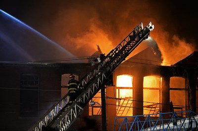 A Haverhill Fire Department ladder truck continues to douse water on the flames consuming the vacant mill building at 30 Stevens St. well after the sun had set on Sept. 20, 2015.
