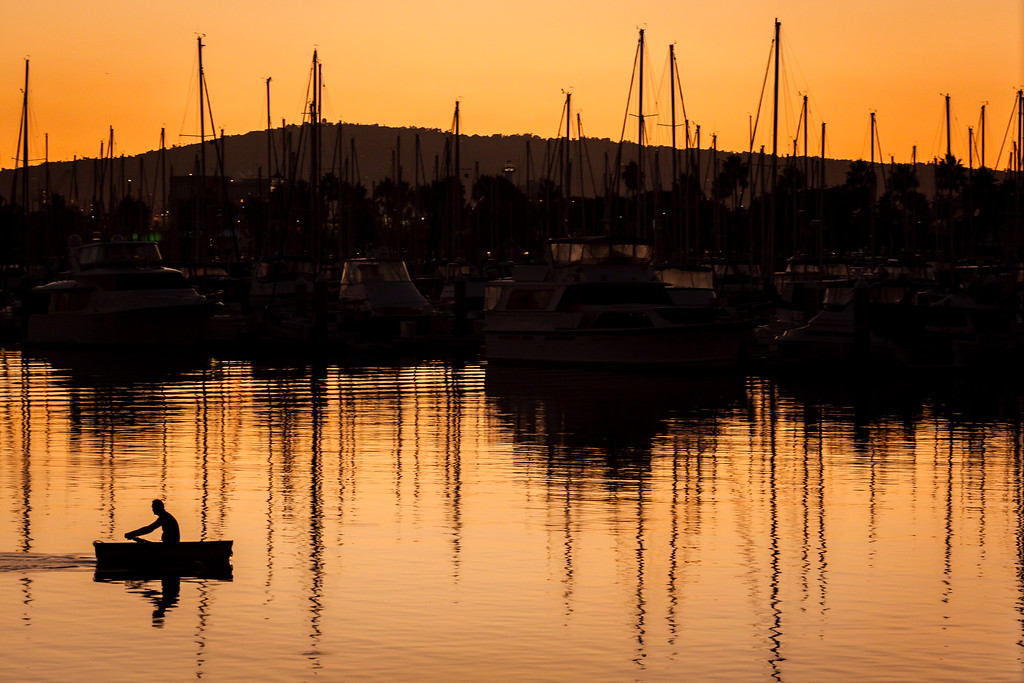 Serene rowboat heads home after sunset in the Harbor in Long Beach California