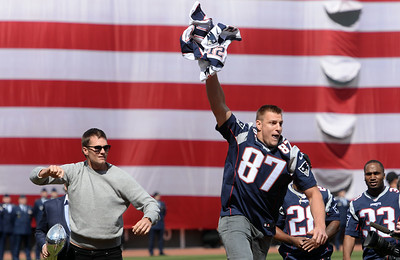 New England Patriots tight end Rob Gronkowski snags Tom Brady's recently-recovered Super Bowl LI jersey as Brady presents it to the fans at Fenway Park for the Red Sox Opening Day festivities on April 3, 2017.