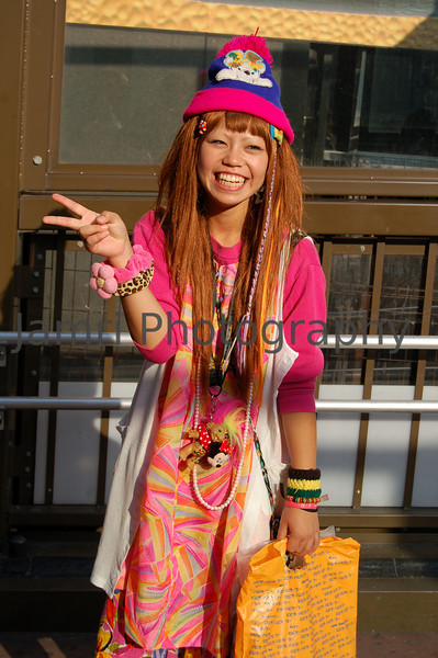 """Title: """"Hippy Girl""""<br /> Category: Street Portrait<br /> Location: Shinsaibashi, Osaka, Japan<br /> Notes: Ritsuko and I were walking through Shinsaibashi with our friend Pastor Jeff MacKay and suddenly he called over this girl and asked her to pose for me. I'm not sure if he knew her or it was just random. One interesting thing I noticed about a year and a half later when I was showing this photo the buyer of this camera and lens as an example, was one of her bands had """"W.W.J.D."""" on it. This made me suspect that she was someone Jeff knew, but I still haven't asked Jeff about this. Then I read somewhere that Japanese noticed many American Sports Stars wearing """"W.W.J.D."""" bands that these have been copied and now sell in sport shops here (I've not seen any for sale personally). Taken with a Nikon D50 camera + kit Nikkor 18-55 (non VR, version 1) lens."""