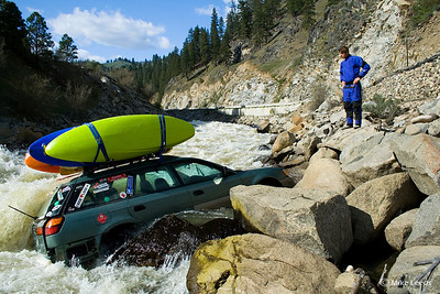 "My friend Brent trying to figure out how he is going to get his boat that is about to fall in.  Juicer Rapid on the North Fork Payette River in Idaho.  This photo has also been featured in ""Paddler Magazine"".  July/August 08."