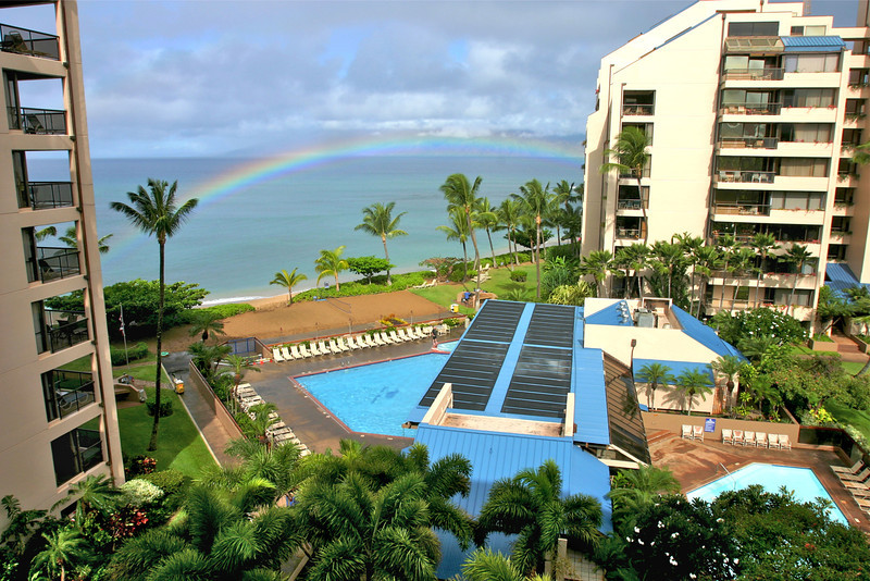 As we awaken to an early morning rainbow we can see Molokai in the distance.  The view from our room on the fifth floor, while staying at the Sands of Kahana, Lahaina, Maui, overlooks the pool complex, clear water beaches and coral reefs.