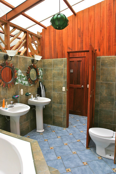 Adjacent to the front door the Howler Room entrance, at the Banana Azul, Puerto Viejo de Talamanca, Limon, Costa Rica, leads into a spacious bathroom complete with jacuzzi, shower and windowless jungle view.