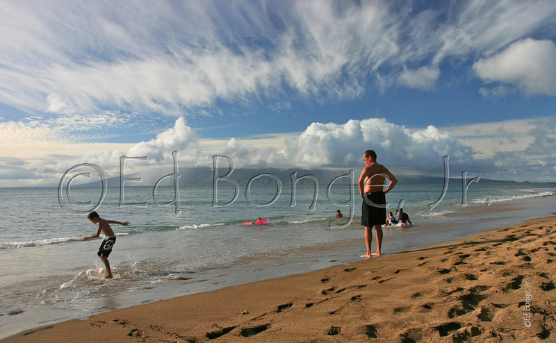 Beach boarding at the Sands of Kahana, Maui, while distant rain showers mist the shores of Molokai