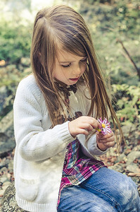 Girl Playing With A Flower