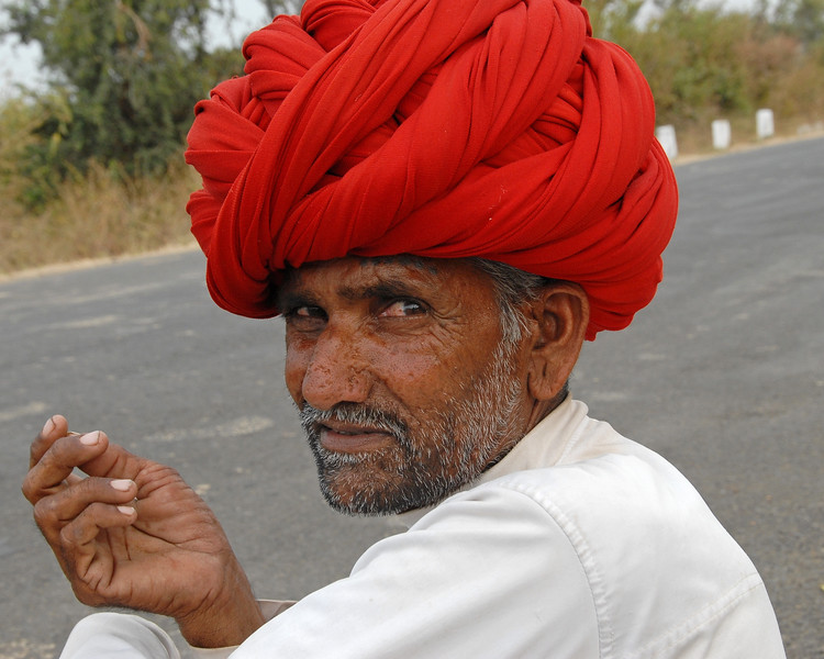 India: This man with his family from Rajasthan dressed in his traditional way was travelling with his family in Maharshtra State and were sitting waiting for a ride in a village near Nagpur, Maharashtra. Jan 2007.