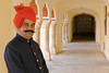 Portrait of the attendant wearing a red turban and standing in the corridor of the Jaipur Palace, Jaipur, Rajasthan, India.