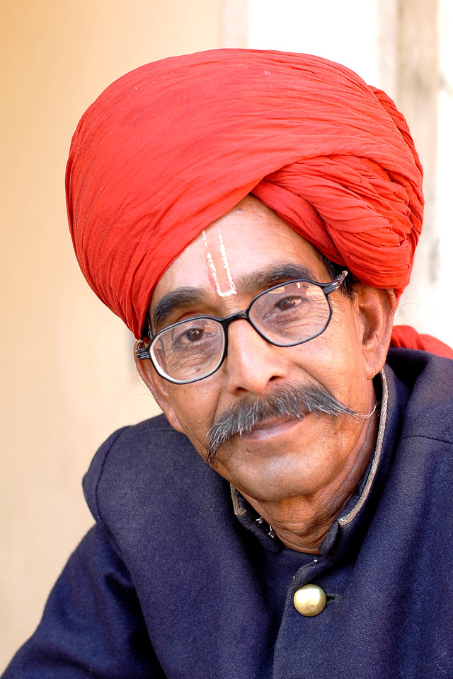 Close portrait of the attendant at the Jaipur Palace, Jaipur, Rajasthan, India wearing the red turban and blue jacket (sherwani).