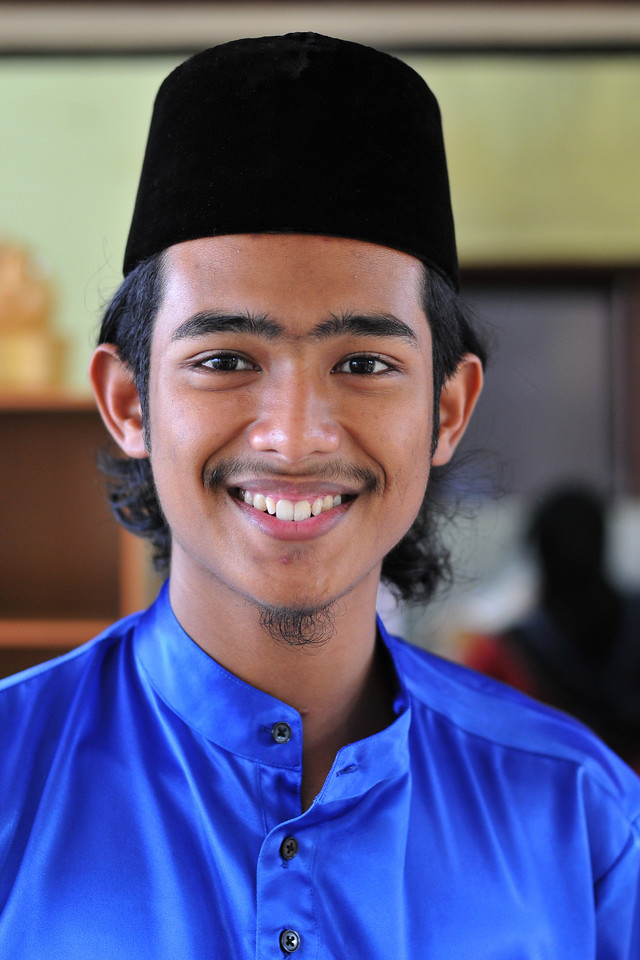 Young staff member at Malay village recreated with houses, music, and dance in Langkawi, Malaysia