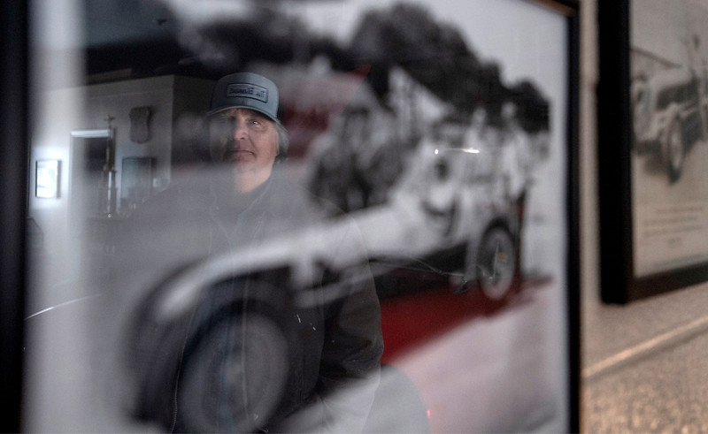 Tom Barbour's reflection is seen on the glass of one of the historic automotive photographs hanging on the wall of his garage in Fort Collins, Colo. on Thursday, Feb. 18, 2021. As a longtime antique car enthusiast, Barbour helped his friend Rene Eles retrieve the engine for his Maserati Mistral after Eles' storage unit was liquidated.
