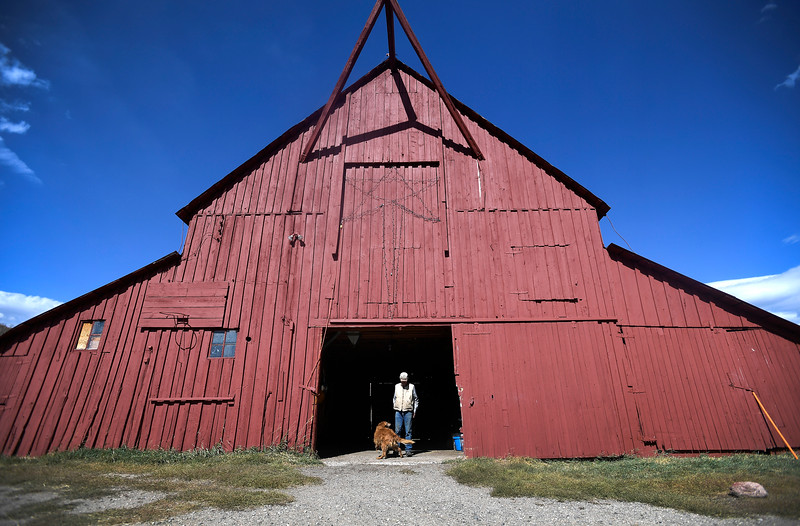 Jay Fetcher stands in the doorway of his barn with his Golden Retriever at his Clark Ranch north of Steamboat Springs, Colo. on Wednesday, Oct. 9, 2019. Fetcher has ranched these fields the nearly 70 years he's lived in the Upper Elk River Valley.