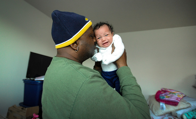 Terrance Harris holds his three-week-old daughter Belah in their new rental home in North Bend, Ore. on Tuesday, Dec. 5. 2017. The family had been homeless for more than two years after they were given a no-cause eviction in the summer of 2015.