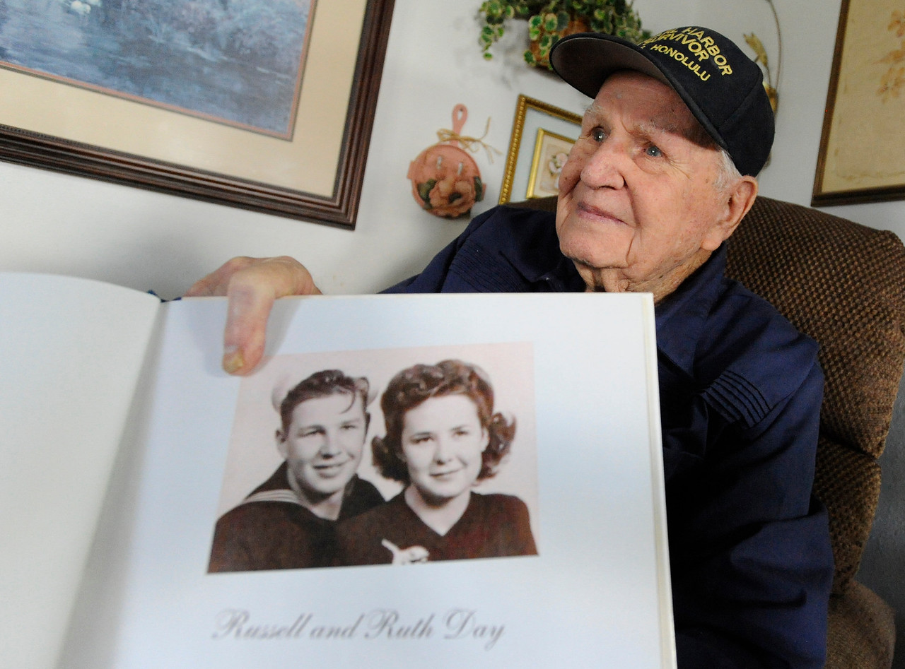 Russ Day, a Navy veteran, shows a photo of him and his wife as he recalls his experience at Pearl Harbor on December 7, 1941.