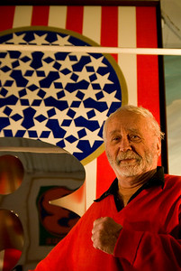 "Robert Indiana stands in front of the chrome birthday ""8"" with the backdrop of his American Flag redesigned as the original creator of the flag wanted it. Robert Indiana, iconic 1960s artist"