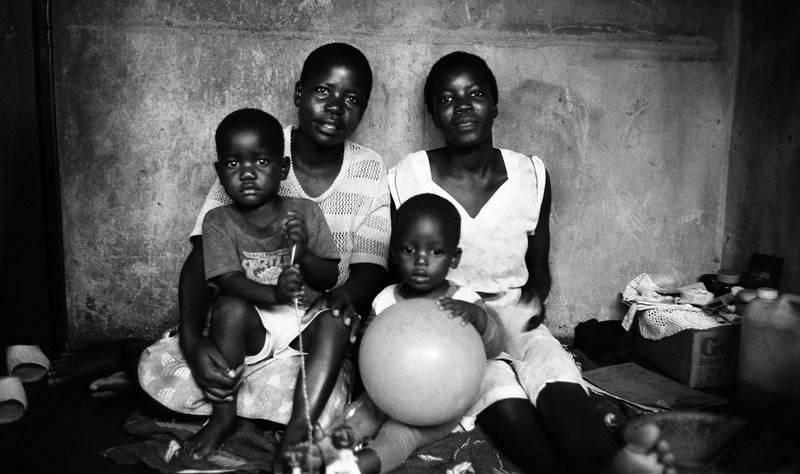 """Meeting's wife, with her sister, her nephew and her son David, in the main room of their """"Kaya"""", Harare, Zimbabwe (1993) © Copyrights Michel Botman Photography"""