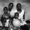 "Meeting's wife, with her sister, her nephew and her son David, in the main room of their ""Kaya"", Harare, Zimbabwe (1993) © Copyrights Michel Botman Photography"