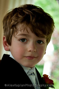 Young boy with brown hair smiling for the camera wearing a tuxedo with a white vest and white tie and an orange and yellow corsage  by Alex Kaplan, photographer http://www.alexkaplanphoto.com