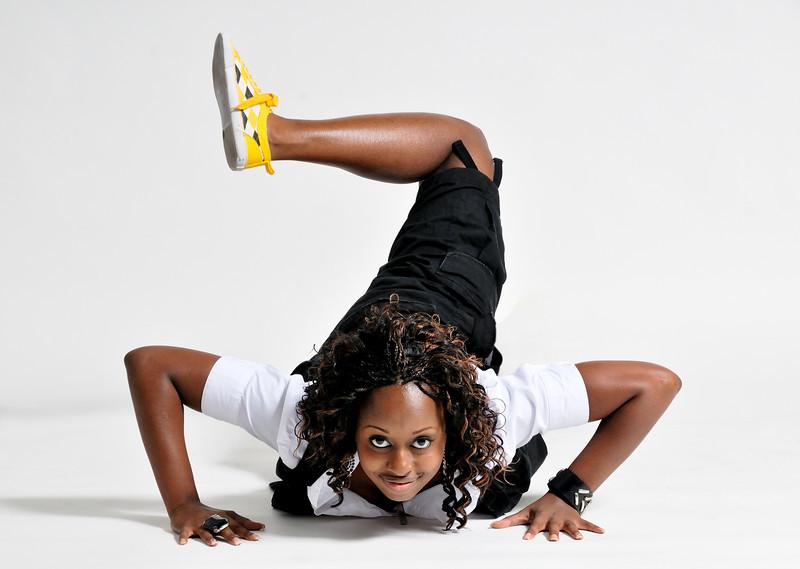 Young woman wearing a white shirt black shorts and yellow and white sneakers posing with her hands on the floor and her leg up in the air Alex Kaplan Photographer https://professionalheadshots.com
