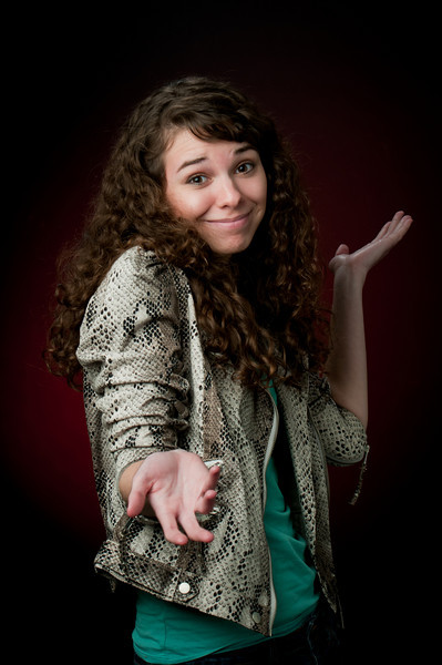 Girl with brown curly hair wearing a snakeskin jacket and a teal shirt looking confused at the camera and holding her hands up in the air Alex Kaplan Photographer https://professionalheadshots.com