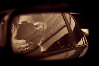 Reflection of a photographer wearing a ring in the side view mirror of a car by Alex Kaplan, photographer http://www.alexkaplanphoto.com