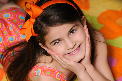 Close up of a young girl with brown hair wearing a colorful dress and an orange bow headband in her hair smiling as she rests her head on her hands Alex Kaplan Photographer https://professionalheadshots.com