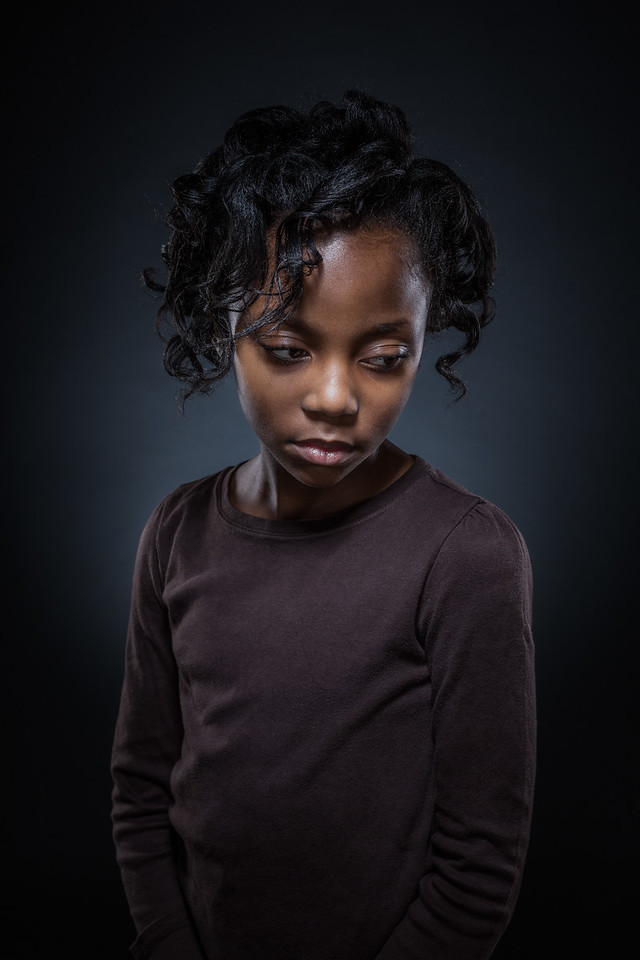 A young African American girl on blue.